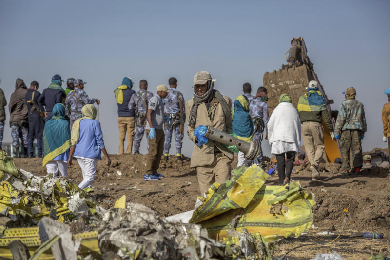 Workers gather at the scene of an Ethiopian Airlines flight crash near Bishoftu, or Debre Zeit, south of Addis Ababa, Ethiopia, Monday, March 11, 2019. A spokesman says Ethiopian Airlines has grounded all its Boeing 737 Max 8 aircraft as a safety precaution, following the crash of one of its planes in which 157 people were killed. (AP Photo/Mulugeta Ayene)