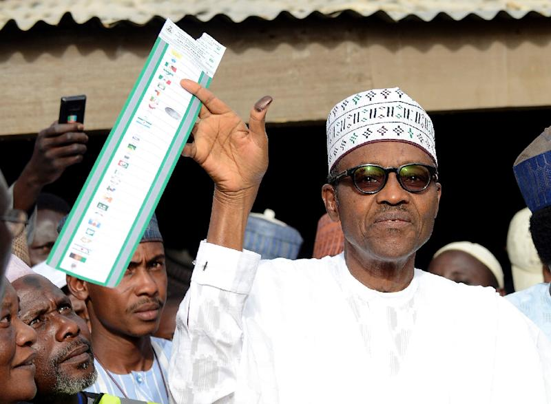 Main opposition All Progressives Congress (APC) presidential candidate Mohammadu Buhari holds up his ballot paper prior to voting in Daura, in northern Nigeria's Katsina State, on March 28, 2015 (AFP Photo/Pius Utomi Ekpei)