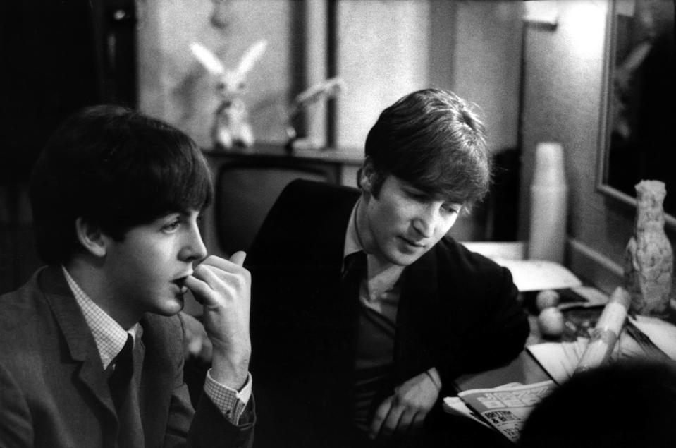 Paul McCartney and John Lennon (1940-1980) from The Beatles posed backstage at the Finsbury Park Astoria, London during the band's Christmas Show residency on 30th December 1963.  (Photo by Val Wilmer/Redferns)