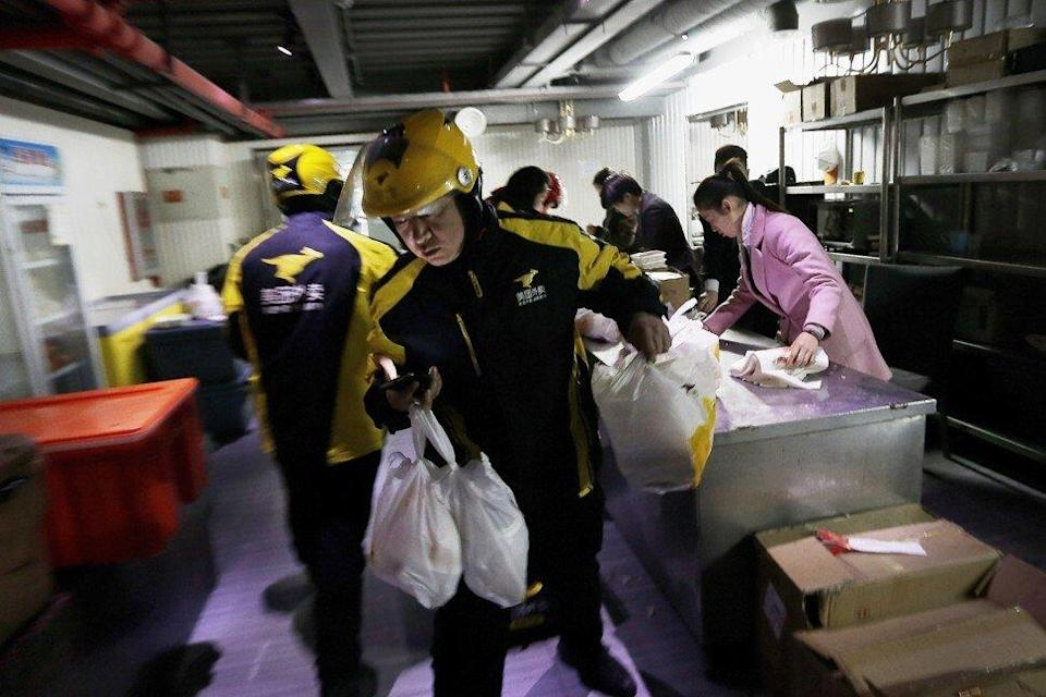 Couriers from Meituan, operator of China's largest local services e-commerce platform, are seen handling food orders for delivery from a centre in Beijing. Photo: AP