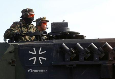 German army soldiers drive their battle tank Leopard 2 after NATO exercise in Pabrade