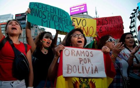 People celebrating Bolivian President Evo Morales' resignation, in Buenos Aires - Credit: JOSE LUIS PERRINO/AFP
