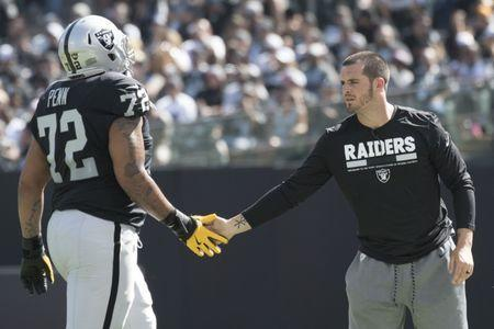 FILE PHOTO: October 8, 2017; Oakland, CA, USA; Oakland Raiders quarterback Derek Carr (right) high-fives offensive tackle Donald Penn (72) against the Baltimore Ravens during the first quarter at Oakland Coliseum. Mandatory Credit: Kyle Terada-USA TODAY Sports