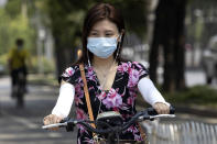 A woman wearing a mask to curb the spread of the new coronavirus rides an electric bike on the streets of Beijing on Friday, June 19, 2020. China declared a fresh outbreak in Beijing under control after numbers for new cases stabilized as hundreds of thousands are tested. (AP Photo/Ng Han Guan)