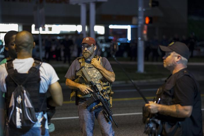 Members of the Oath Keepers walk with their personal weapons on the street during protests in Ferguson, Missouri August 11, 2015. Police in riot gear clashed with protesters who had gathered in the streets of Ferguson early on Tuesday to mark the anniversary of the police shooting of an unarmed black teen whose death sparked a national outcry over race relations. REUTERS/Lucas Jackson
