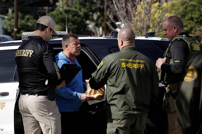 Paul Flores, second from left, talks to authorities after being pulled from a Los Angeles County Sheriff's Department vehicle outside of a San Pedro home being searched in connection with the case Wednesday, Feb. 5, 2020, in Los Angeles. Search warrants were served Wednesday at locations in California and Washington state in the investigation of the disappearance of Kristin Smart, the Cal Poly student who disappeared in 1996.