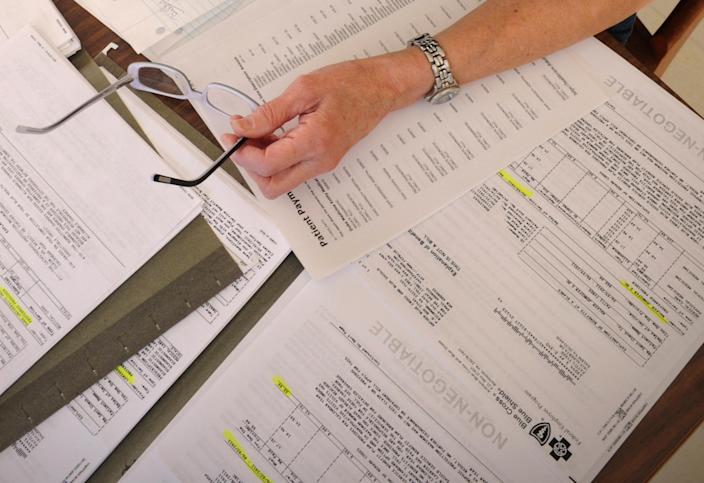 FILE - In this Dec. 20, 2011 file photo medical bills are spread out on the kitchen table of a cancer patient in Salem, Va. Hospitals across the country, and even within the same city, sometimes charge tens of thousands of dollars more for the same procedures, according to figures the government released for the first time Wednesday, May 8, 2013. (AP Photo/Don Petersen, File)