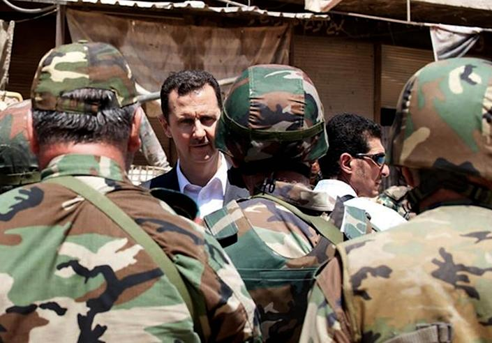 FILE - This file image posted on the official Facebook page of the Syrian Presidency on Thursday, Aug. 1, 2013 purports to show Syrian President Bashar Assad talking with soldiers with during Syrian Arab Army day in Darya, Syria. More than two years into Syria's civil war, the once highly-centralized authoritarian state has effectively split into three distinct parts, each boasting its own flags, security agencies and judicial system. (AP Photo/Syrian Presidency via Facebook, FIle)