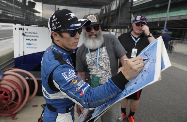 Takuma Sato, of Japan, signs an autograph for a fan on the opening day of practice for the Indy 500 auto race at Indianapolis Motor Speedway in Indianapolis, Tuesday, May 15, 2018. (AP Photo/Michael Conroy)