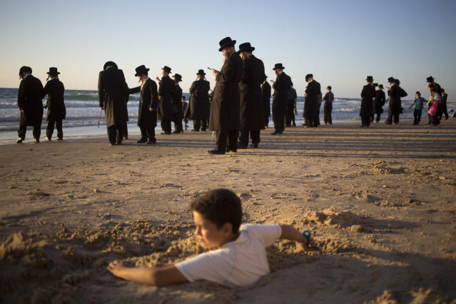 "<p>A boy is covered in sand as ultra-Orthodox Jewish men of the Vizhnitz Hassidic sect pray at Mediterranean Sea shore as they participate in a Tashlich ceremony, in Herzeliya, Israel, Thursday, Sept. 28, 2017. Tashlich, which means ""to cast away"" in Hebrew, is the practice in which Jews go to a large flowing body of water and symbolically ""throw away"" their sins by throwing a piece of bread, or similar food, into the water before the Jewish holiday of Yom Kippur, which starts at sundown Friday. (Photo: Ariel Schalit/AP) </p>"