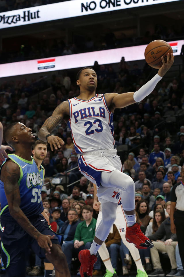 Philadelphia 76ers guard Trey Burke (23) makes a layup in front of Dallas Mavericks guard Delon Wright (55) during the first half of an NBA basketball game in Dallas, Saturday, Jan 11, 2020. (AP Photo/Michael Ainsworth)
