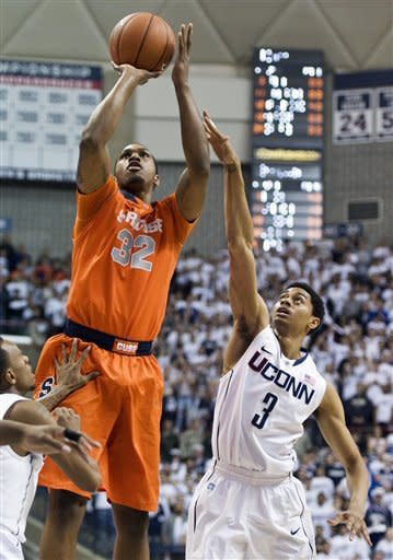 Syracuse's Kris Joseph (32) shoots over Connecticut's Jeremy Lamb in the first half of an NCAA college basketball game in Storrs, Conn., Saturday, Feb. 25, 2012. (AP Photo/Jessica Hill)