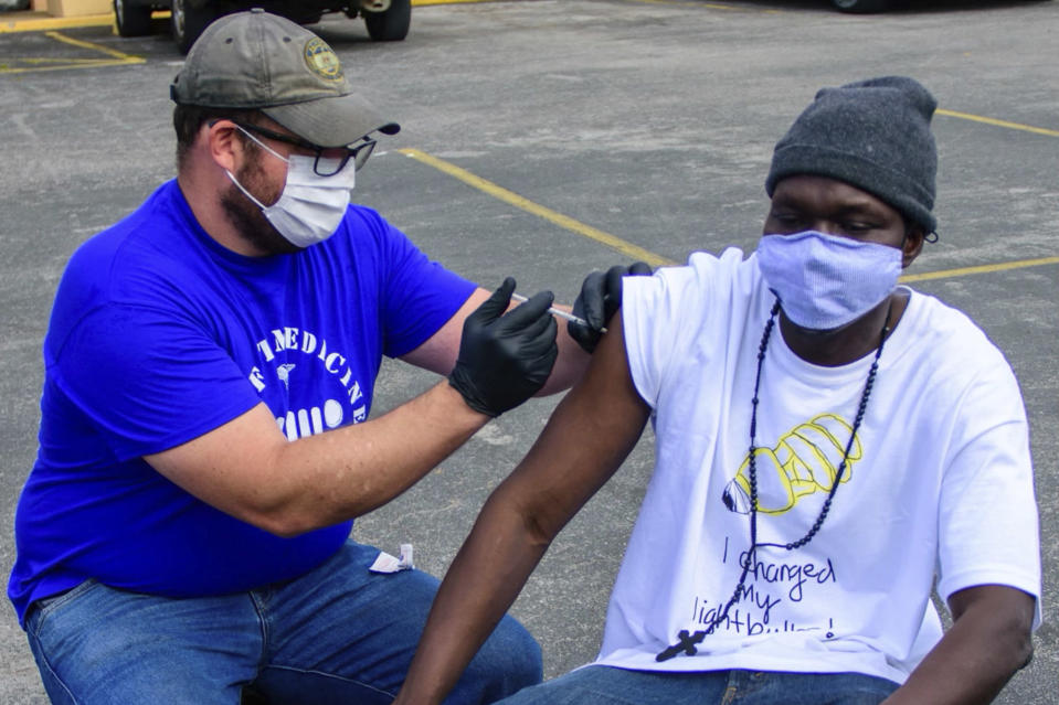In this April 7, 2021, photo provided by Neighborhood Health, Dr. Pete Cathcart vaccinates Deng Autiak in Nashville. With vaccine supplies increasing in the U.S., the shots are finally reaching thousands of Americans who are homeless. In Nashville, many organizations have set a goal of bringing vaccine to everyone experiencing homelessness by Memorial Day. (Jeremy McCraw/Neighborhood Health via AP)