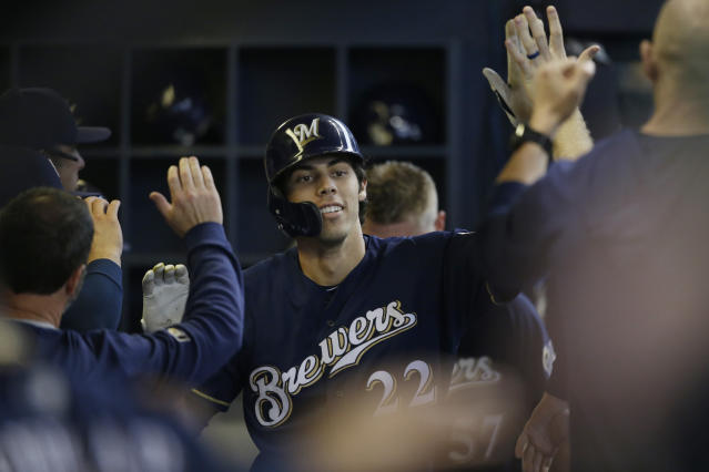 Milwaukee Brewers' Christian Yelich reacts with teammates in the dugout after his home run against the Pittsburgh Pirates during the sixth inning of a baseball game Sunday, June 9, 2019, in Milwaukee. (AP Photo/Jeffrey Phelps)
