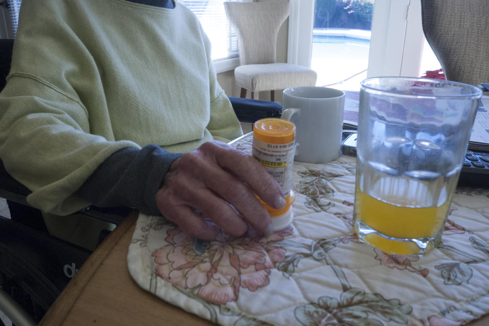 An elderly woman reaches for a pill bottle on a table with a glass of orange juice.