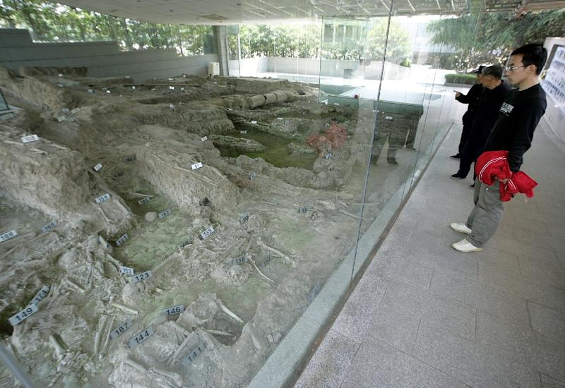Chinese visitors view the remains of a mass grave at the Nanjing Massacre Memorial Hall (AFP Photo/Liu Jin)