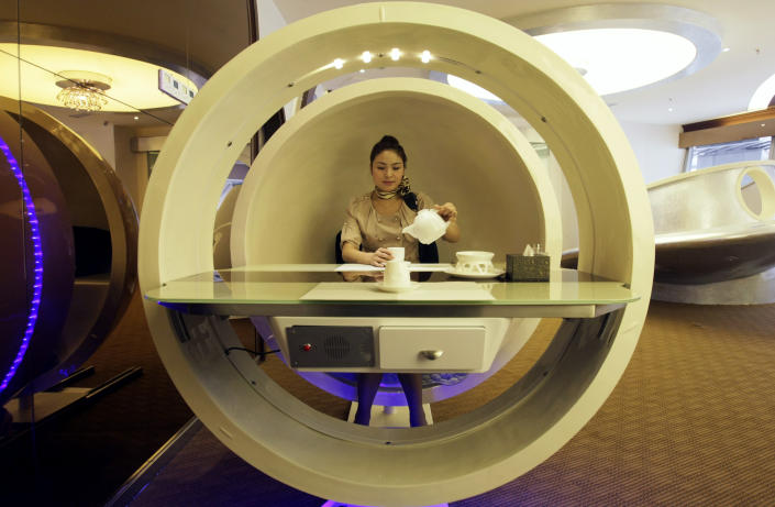 """A waitress poses inside an egg-shaped dining booth at an A380 theme restaurant during a media event before its official opening in Chongqing municipality, April 25, 2012. The restaurant, named """"Special Enjoyment"""" (Chinese name """"Special Class""""), is about 600 square metres in size, including the six private rooms, and can serve up to 110 customers, local media reported. The restaurant officially started business on May 1, 2012. REUTERS/Stringer"""
