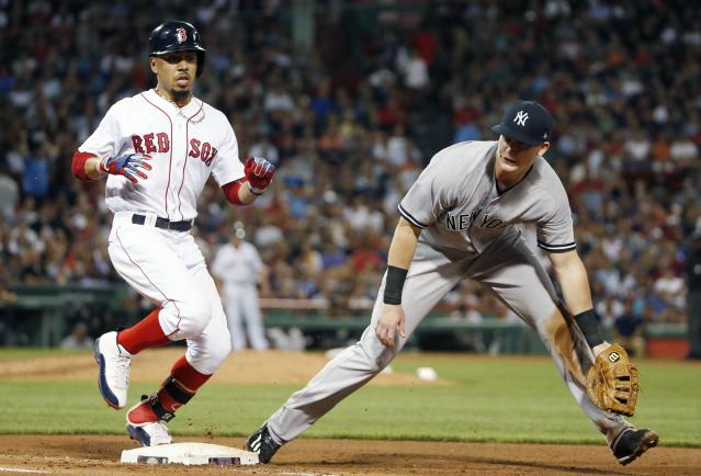 Boston Red Sox's Mookie Betts, left, singles after the throwing error from New York Yankees' Starlin Castro gets past New Garrett Cooper, right, allowing Betts to advance during the sixth inning of the second game of a baseball doubleheader in Boston, Sunday, July 16, 2017. (AP Photo/Michael Dwyer)