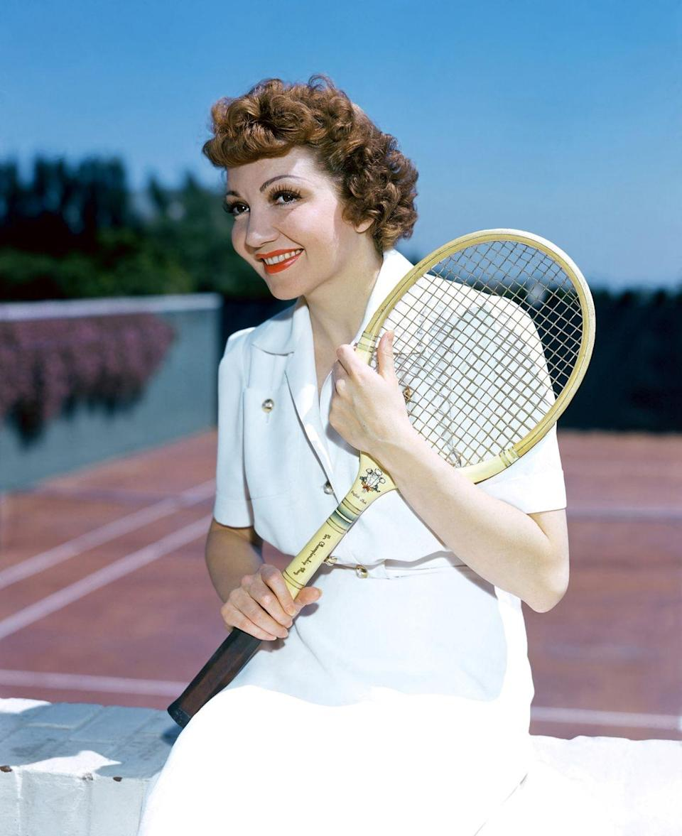 <p>Claudette Colbert is dressed in her tennis whites as she gets ready to hit the court, circa 1930. </p>