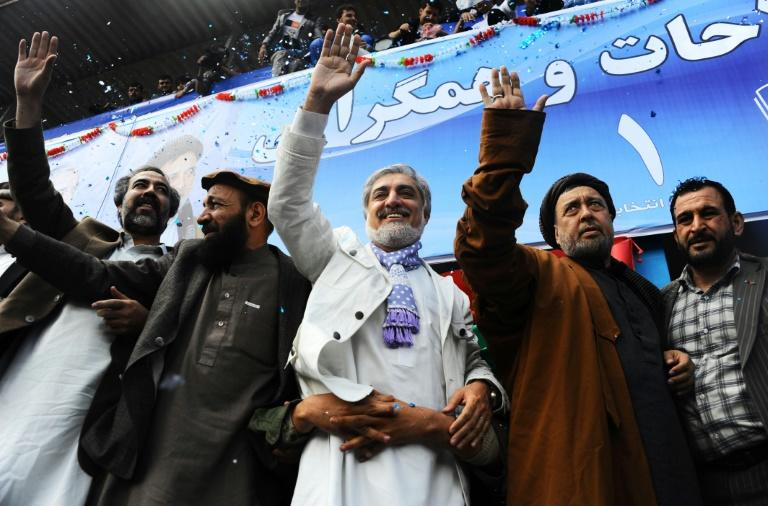 Afghan presidential candidate Abdullah Abdullah (C) and vice-presidential candidates Mohammad Mohaqiq (2nd R) and Mohammad Khan (2L) wave to supporters during a campaign rally in 2014