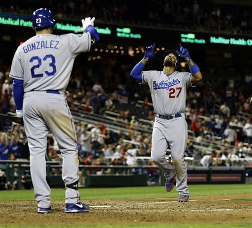 Los Angeles Dodgers' Matt Kemp (27) celebrates as he scores his solo home run, with Adrian Gonzalez (23), during the ninth inning of the second baseball game of a doubleheader against the Washington Nationals at Nationals Park, Wednesday, Sept. 19, 2012, in Washington. Kemp's homer was the game-winner and the Dodgers won the second game 7-6. (AP Photo/Alex Brandon)