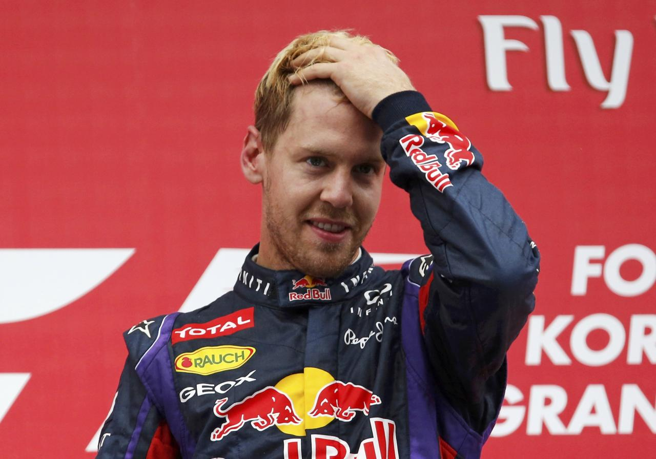 Red Bull Formula One driver Sebastian Vettel of Germany gestures on the podium after winning the Korean F1 Grand Prix at the Korea International Circuit in Yeongam, October 6, 2013. REUTERS/Kim Hong-Ji (SOUTH KOREA - Tags: SPORT MOTORSPORT F1)