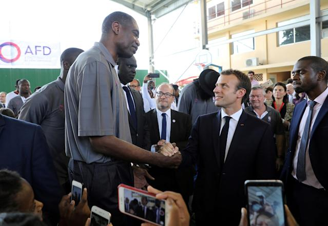 French President Emmanuel Macron greets a former pro basketball player from NBA Africa at the French Louis Pasteur high school in Lagos, Nigeria, July 4, 2018. Ludovic Marin/Pool via Reuters