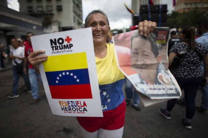 """A supporter of President Nicolas Maduro holds on her left hand a poster that in Spanish reads """"No more Trump"""" and on her right an image of Late President Hugo Chavez, during an anti-imperialist rally in Caracas, Venezuela, Saturday, August 31, 2019. Venezuelan officials say they have proof of paramilitary training camps operating in neighboring Colombia where groups are purportedly plotting attacks to undermine President Nicolás Maduro. (AP Photo/Ariana Cubillos)"""