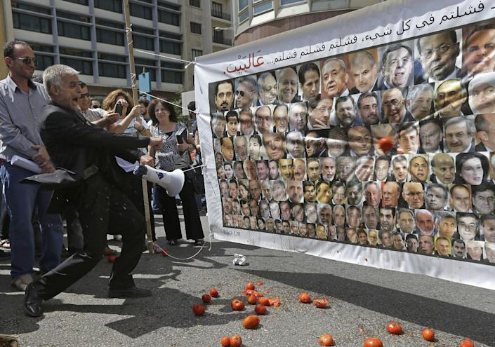 """FILE -- In this May 31, 2013, file photo, a Lebanese protester, left, throws tomatoes at a banner with the portraits of the 128 Lebanese lawmakers with Arabic that reads, """"you failed in everything, failed failed failed, go home,"""" during a protest against the 17 months extension of the Lebanese parliament, near the parliament building in Beirut, Lebanon. Since the current parliament was elected in June 2009, the lawmakers have met 21 times to pass 169 laws, mostly related to raise government and civil servants' salaries, receive foreign aid and amend election law that will enable their re-election. In 2013, Lebanon's lawmakers only met twice to pass two laws, one of which was to extended their mandate for 18 months. (AP Photo/Hussein Malla, File)"""