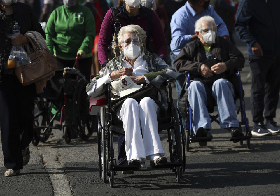 Elderly people are wheeled away after getting their shot of the COVID-19 Pfizer vaccine in Mexico City, on Monday, March 8, 2021. (AP Photo / Marco Ugarte)