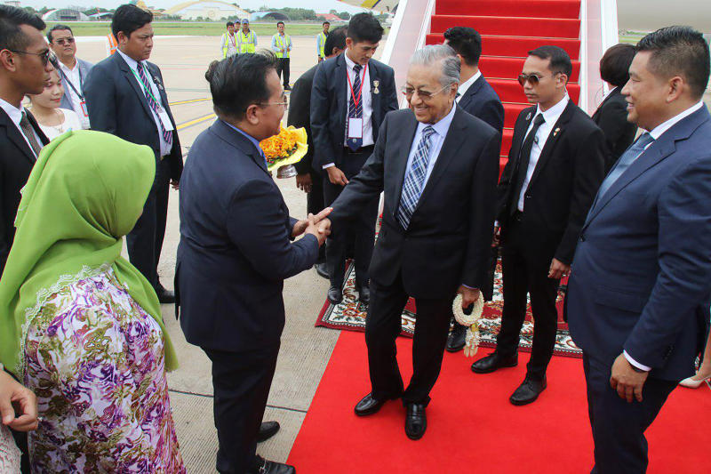 In this photo provided by Agence Kampuchea Presse (AKP), Malaysian Prime Minister Mahathir Mohamad, center, is welcoming by Cambodian government officers upon his arrival at Phnom Penh International Airport, in Phnom Penh, Cambodia. Mahathir Mohamad of Malaysia has arrived in Cambodia for a three-day official visit to strengthen the two countries' bilateral relationship. (Khem Sovannara, Agence Kampuchea Presse via AP)