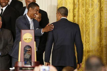 UConn men's basketball head coach Kevin Ollie (L) pats U.S. President Barack Obama (R) on the shoulder after a ceremony honoring the NCAA champion University of Connecticut Huskies men's and women's basketball teams in the East Room of the White House in Washington, June 9, 2014. REUTERS/Jim Bourg