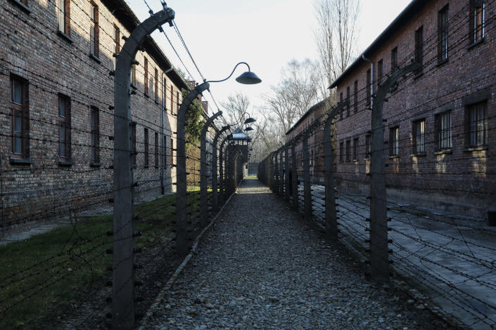 A pathway leading to an observation and security tower between what were electric barbed wire fences inside the former Nazi death camp of Auschwitz I in Oswiecim, Poland, Sunday, Dec. 8, 2019. The commemorations for the victims of the Holocaust at the International Holocaust Remembrance Day, marking the liberation of Auschwitz-Birkenau on Jan. 27, 1945, will be mostly online in 2021 due to the coronavirus pandemic. (AP Photo/Markus Schreiber)