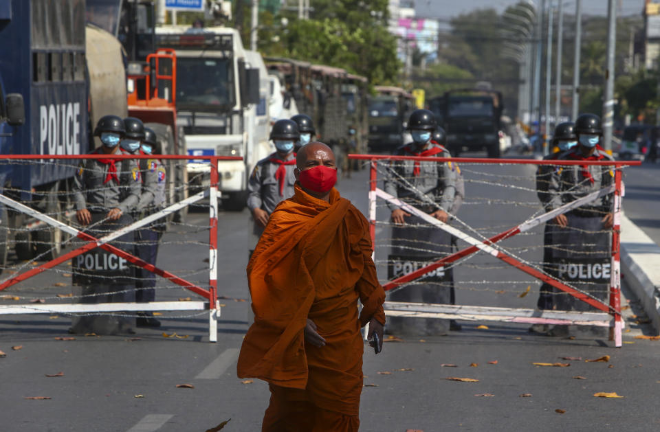 A Buddhist monk walks along a road as police stand watch in Mandalay, Myanmar, Wednesday, Feb. 24, 2021. Protesters against the military's seizure of power in Myanmar were back on the streets of cities and towns on Wednesday, days after a general strike shuttered shops and brought huge numbers out to demonstrate. (AP Photo)