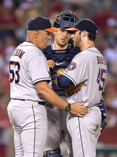 Houston Astros pitching coach Brent Strom, left, talks with relief pitcher Anthony Bass, right, as catcher Jason Castro looks on during the seventh inning of a baseball game against the Los Angeles Angels, Saturday, July 5, 2014, in, Anaheim, Calif. (AP Photo/Mark J. Terrill)