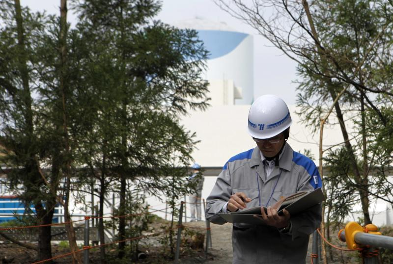 An employee of Kyushu Electric Power Co reads his memo in front of a reactor building at the company's Sendai nuclear power plant in Satsumasendai, Kagoshima prefecture April 3, 2014. While their reactors have been idled, Japan's nuclear plant operators have had to spend around $87 billion to burn replacement fossil fuels. This, in part, explains the utilities' estimated combined losses of around $47 billion as of March, and the $60 billion wiped off the companies' market value. Last week, Kyushu Electric Power Co was confirmed to be seeking a near $1 billion bailout in the form of equity financing from the government-affiliated Development Bank of Japan because of the cost of idling its reactors, joining Hokkaido Electric Power Co which has also asked the bank for financial backing. Picture taken April 3, 2014. REUTERS/Mari Saito (JAPAN - Tags: POLITICS ENERGY ENVIRONMENT)