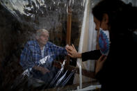 Victor Tripiana, 86, reaches out to touch the hand of his daughter-in-law Silvia Fernandez Sotto, separated by a plastic sheet to prevent the spread of COVID- 19 at the Reminiscencias residence for the elderly in Tandil, Argentina, Sunday, April 4, 2021. Residents here do not have physical contact with their families or leave the residence due to the pandemic, but stay active with group activities within the facility. (AP Photo/Natacha Pisarenko)