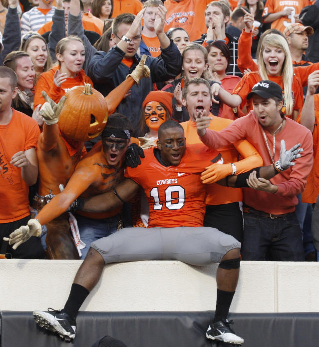 Oklahoma State safety Marelle Martin, center, celebrates with fans following a 59-24 victory over Baylor in an NCAA college football game in Stillwater, Okla., Saturday, Oct. 29, 2011. (AP Photo/Sue Ogrocki)