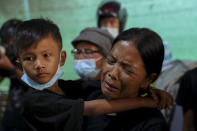 Thida Hnin, right, wife of Thet Naing Win, weeps as her son Aung Phone Khant, left, watches his father's coffin laid in their home in Mandalay, Myanmar, Tuesday, Feb. 23, 2021. Thet Naing Win was shot and killed by Myanmar security forces during an anti-coup protest on Saturday, Feb. 20. (AP Photo)