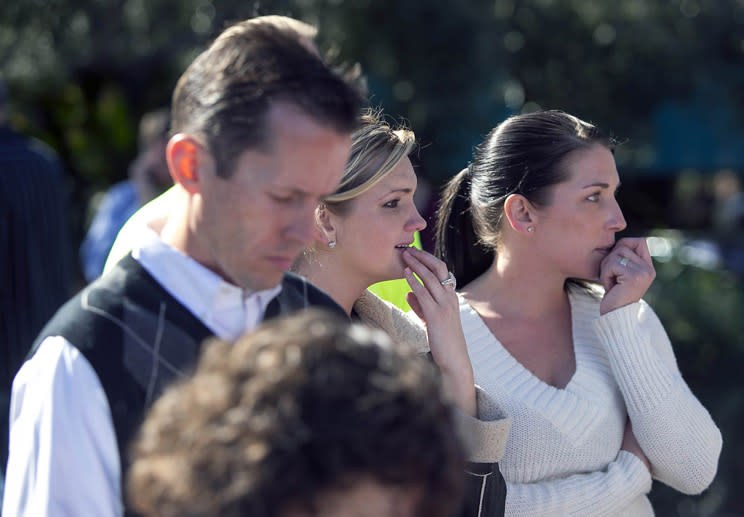 People watch a women being taken to a paramedic truck from an office building where a shooter opened fire in north central Phoenix on Wednesday, Jan. 30, 2013. (AP Photo/The Arizona Republic, Michael Schennum)