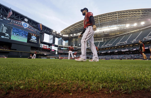 FILE - In this March 25, 2019, file photo, Arizona Diamondbacks' Steven Souza Jr. walks on new turf at the team's home field before an exhibition baseball game against the Chicago White Sox in Phoenix. Baseball's opening day isn't happening in Phoenix or anywhere else on Thursday as planned. The sport is on hold until at least mid-May while the world fights the coronavirus pandemic. If baseball does resume this season, there could be some radical scheduling solutions as MLB tries to squeeze in as many games as possible. (AP Photo/Elaine Thompson, File)