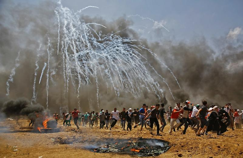 Palestinians run for cover from tear gas during clashes with Israeli security forces near the Gaza border on May 14, 2018 (AFP Photo/MOHAMMED ABED)