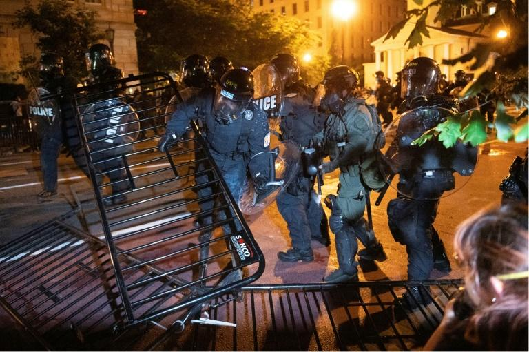 Police charge a barricade in the street during a demonstration against the death of George Floyd near the White House