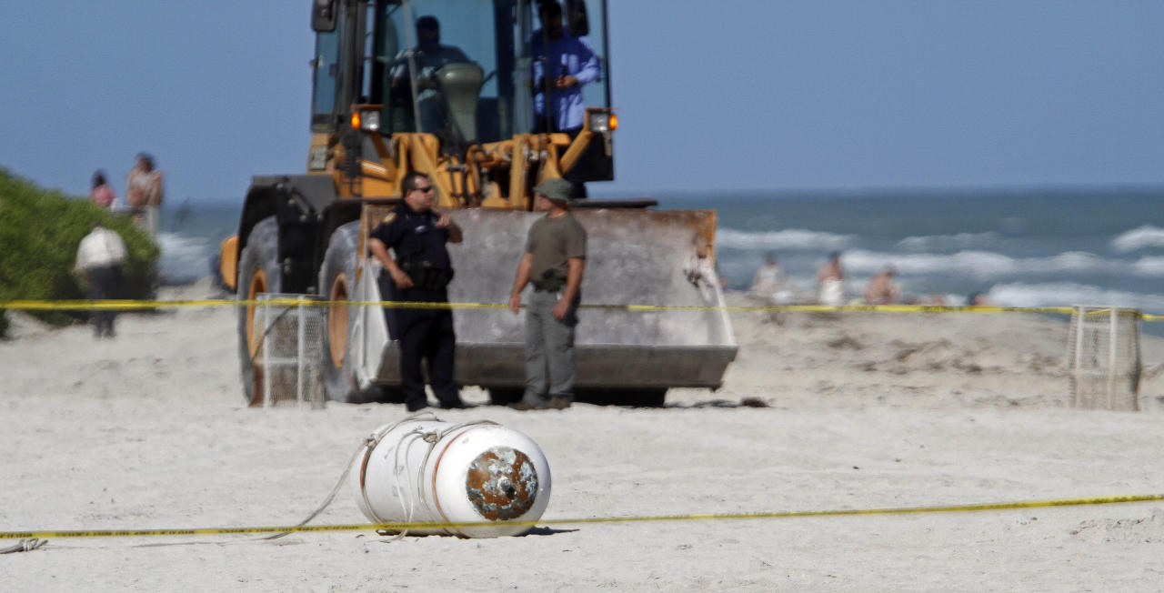 A live Navy training mine that washed ashore is shown at Miami Beach, Fla., Monday, Dec. 5, 2011. Police cordoned off the area around the beached mine with yellow tape Monday and kept bystanders away as Fire Rescue crews and a bomb squad arrived. Fire Rescue spokesman Jesus Sola says photos of the mine have been taken and sent to the Navy, which will remove the device. (AP Photo/Alan Diaz)