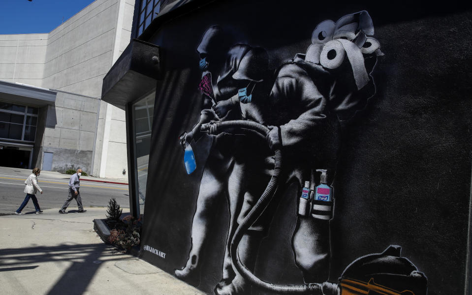 A recently painted mural depicts a coronavirus theme Tuesday, April 14, 2020, in Los Angeles. (AP Photo/Marcio Jose Sanchez)