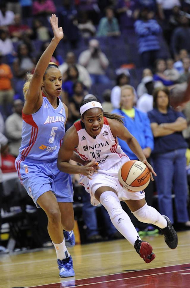Washington Mystics guard Ivory Latta, right, dribbles the ball against Atlanta Dream guard Jasmine Thomas (5) during the first half of Game 2 of the WNBA basketball Eastern Conference semifinal series, Saturday, Sept. 21, 2013, in Washington. (AP Photo/Nick Wass)