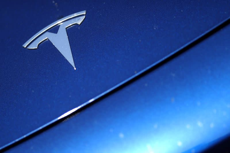 The Tesla logo is seen on a car in Los Angeles
