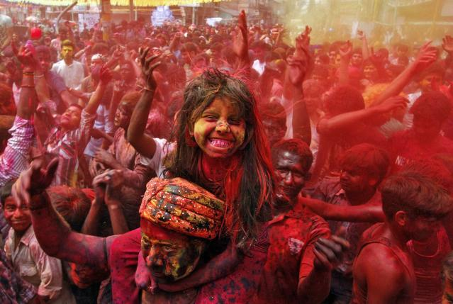 A girl sits on her father's shoulders cheers as she and others daubed in colours dance while celebrating Holi in the northeastern Indian city of Guwahati March 17, 2014. Holi, also known as the Festival of Colours, heralds the beginning of spring and is celebrated all over India. REUTERS/Utpal Baruah (INDIA - Tags: SOCIETY RELIGION TPX IMAGES OF THE DAY)