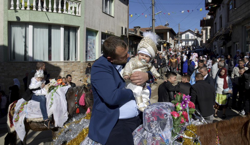 Ismail Atipov holds his son as they take part in a mass circumcision ceremony in the village of Ribnovo, Bulgaria, Sunday, April 11, 2021. Despite the dangers associated with COVID-19 and government calls to avoid large gatherings, Hundreds of people flocked to the tiny village of Ribnovo in southwestern Bulgaria for a four-day festival of feasting, music and the ritual of circumcision which is considered by Muslims a religious duty and essential part of a man's identity. (AP Photo/Jordan Simeonov)