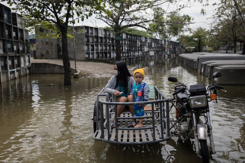 Filipinos visit their departed loved ones in flooded cemetery following Typhoon Molave